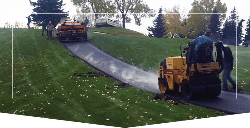 Calgary Paving's asphalt paver working on a pathway between 2 green parks, pathway paving calgary