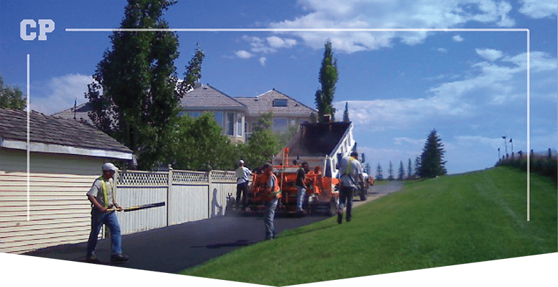 Calgary Paving workers paving a alleyway with a green field next to it and blue sky above them, asphalt driveway, asphalt acreage, diveway and acreage,