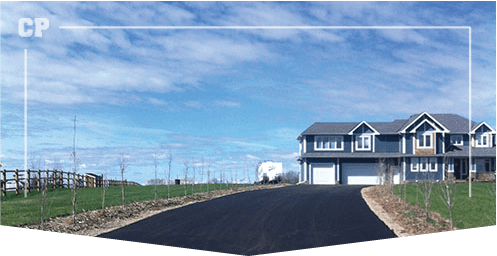 Outdoor photo of an acreage driveway leading up to a big house with beautiful blue sky and green grass all around, driveway completed by Calgary Paving, Parking Lot Paving, asphalt paving image,