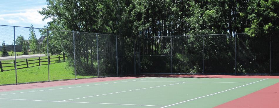 Green tennis court, chainlink fence surrounds it, a green tree is behind the fence, work down by Calgary Paving
